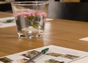bild på penna, papper och en vas med en rosa blomma i konferenslokaler